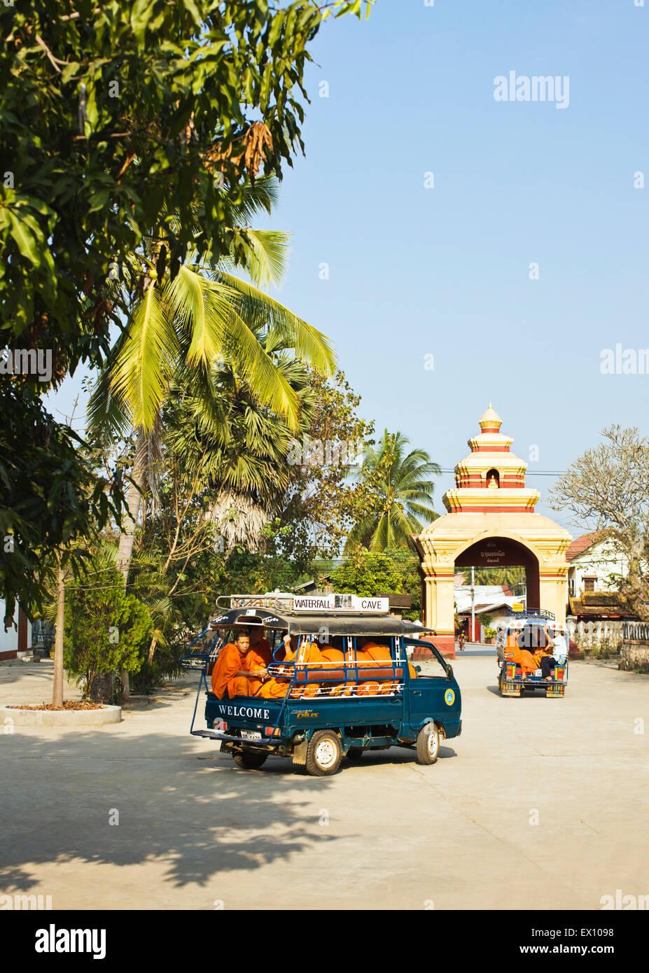 A car load of monks drives off from Wat Manoran. Luang Prabang, Laos Stock Photo