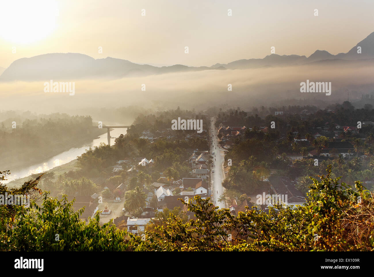 "Luang Prabang at sunrise from the top of Mt. Phou Si. In the Lao language, ""Phou"" means mountain and ""Si"" means - Stock Image"