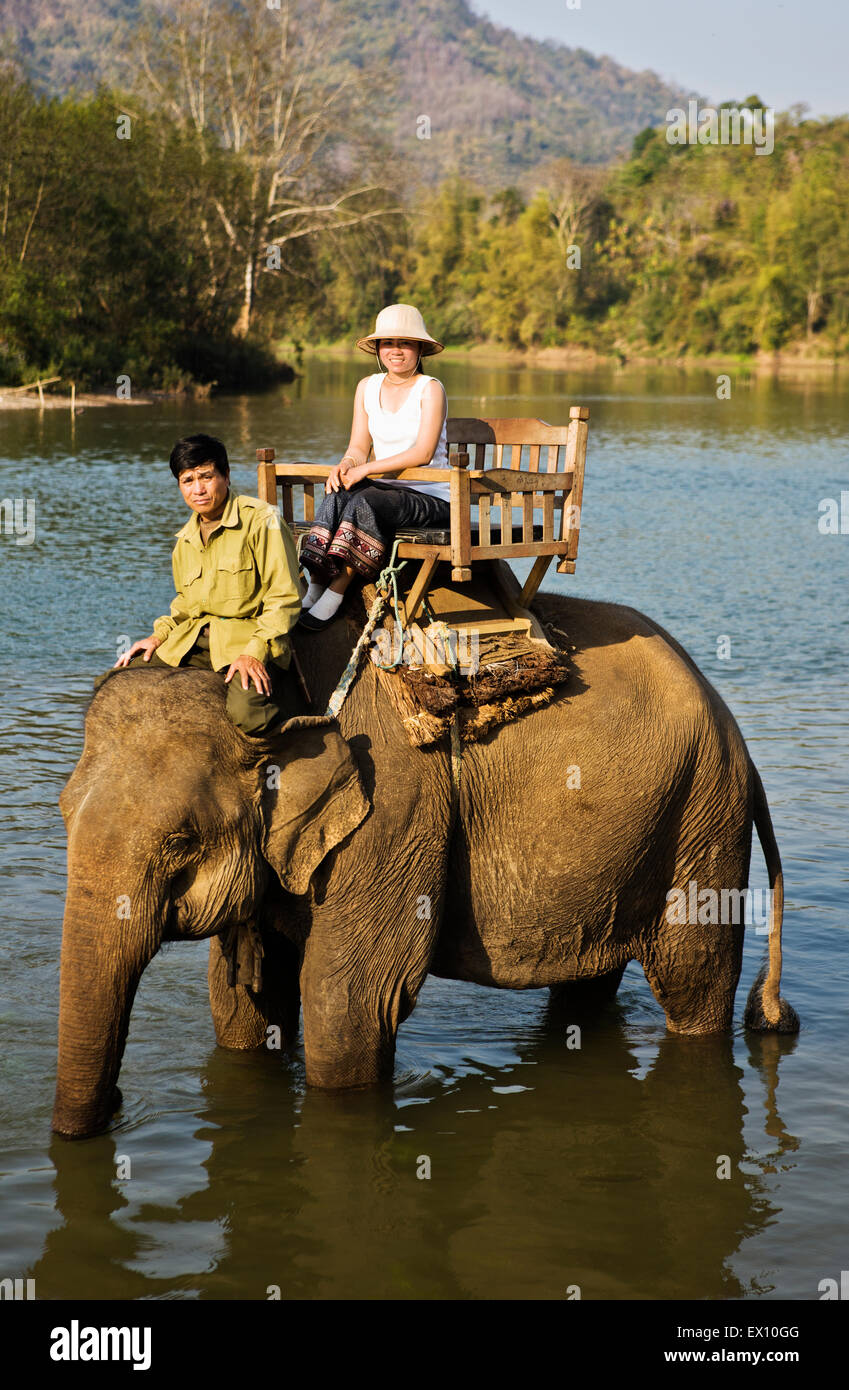 A Lao woman and mahout ride an elephant on the Khan River. - Stock Image