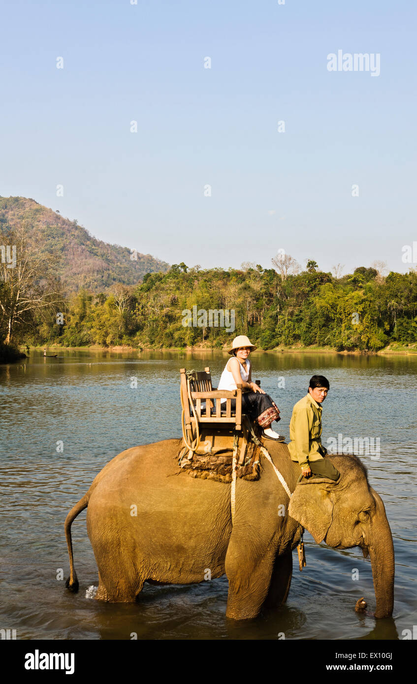 A Lao woman and mahout ride an elephant on the Khan River. Luang Prabang, Laos. - Stock Image