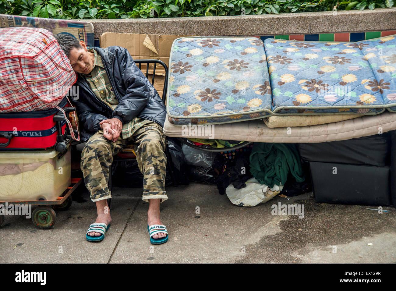 Homeless man asleep in Hong-Kong, China - Stock Image