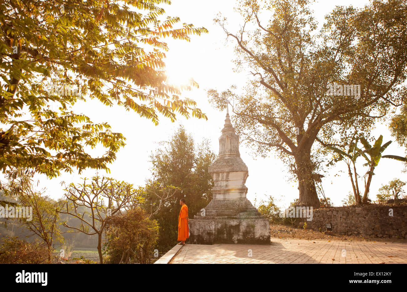 A young monk by Wat Siphoutthabat Thipphuramm at dawn. Luang Prabang , Laos. - Stock Image