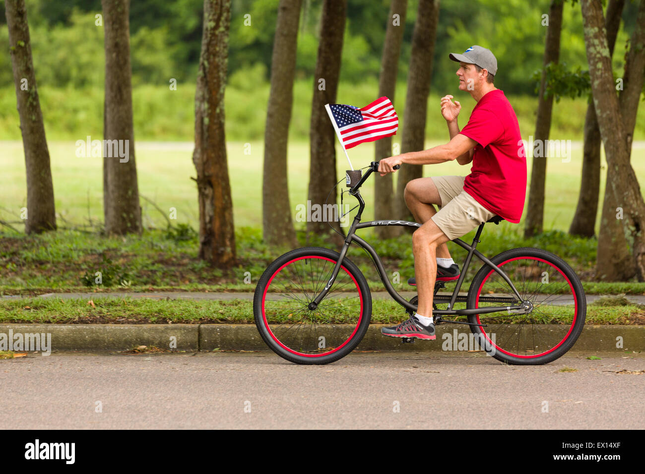 A bicyclist rides past with American flag during the Daniel Island ndependence Day parade July 3, 2015 in Charleston, - Stock Image