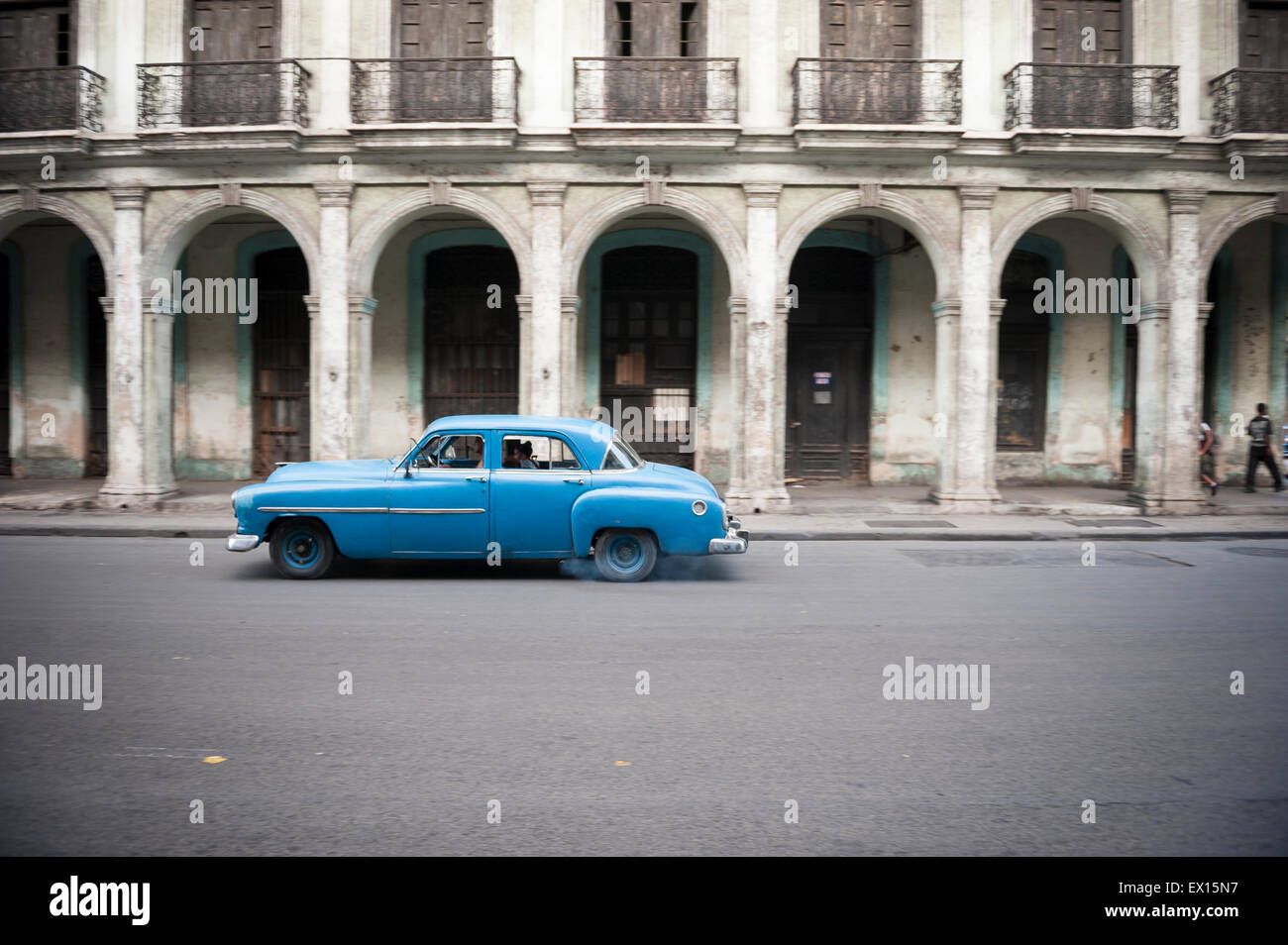 HAVANA, CUBA - JUNE, 2011: Old American car drives in front of the traditional architecture of a colonial arcade. - Stock Image