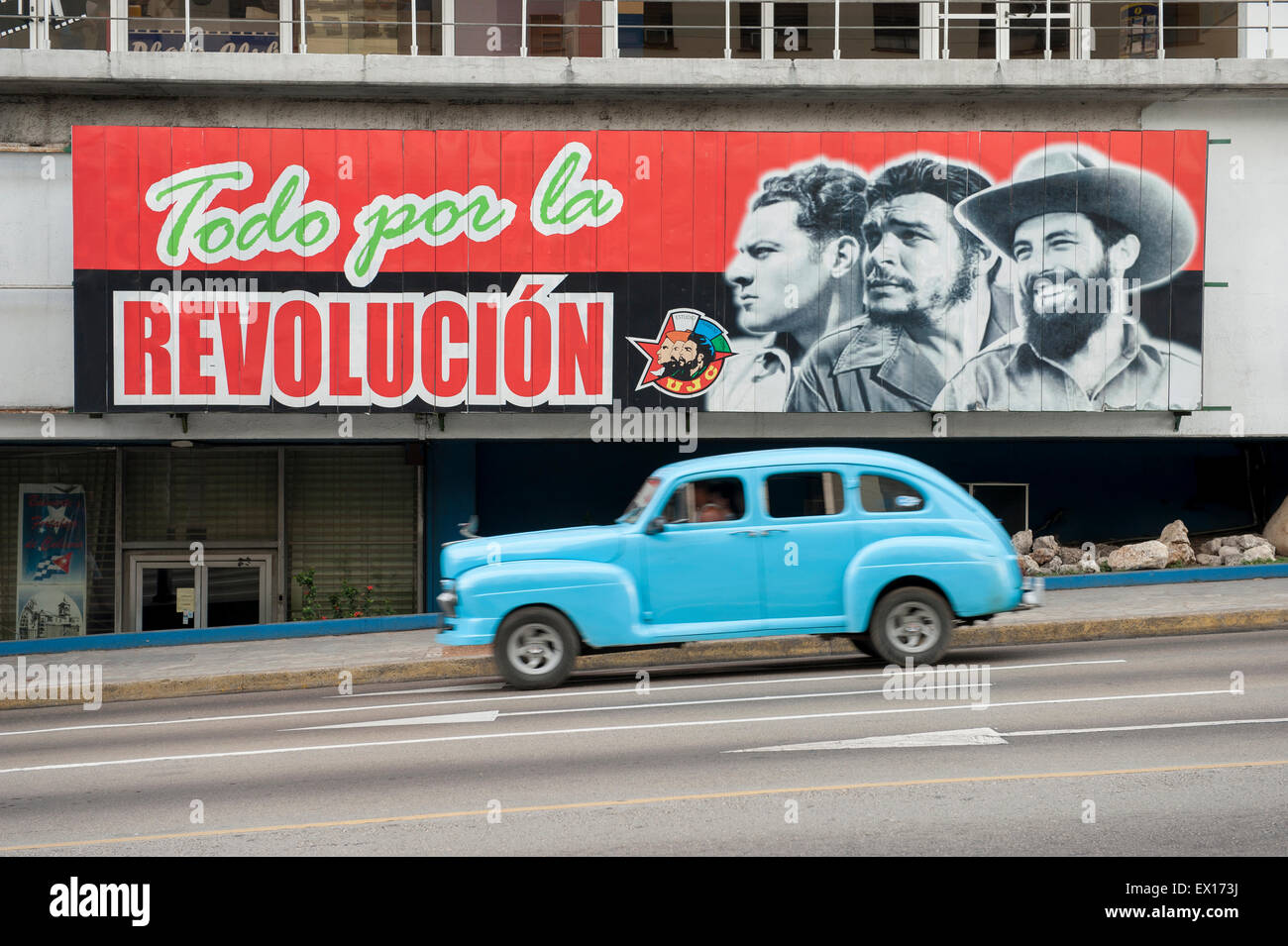 HAVANA, CUBA - JUNE, 2011: Vintage American taxi car passes below billboard promoting Communist propaganda in the - Stock Image