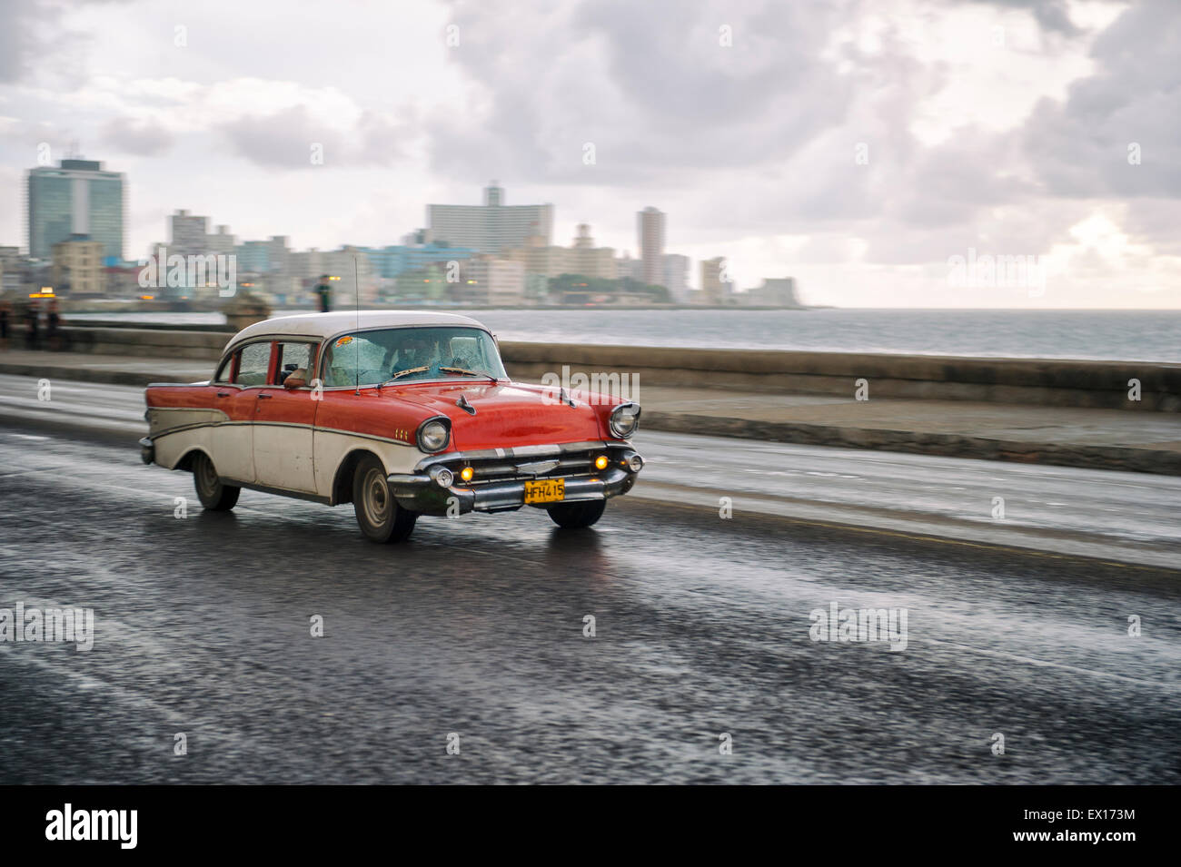HAVANA, CUBA - JUNE 13, 2011: Classic old fashioned 50s car passes in front of the city skyline along the seafront - Stock Image