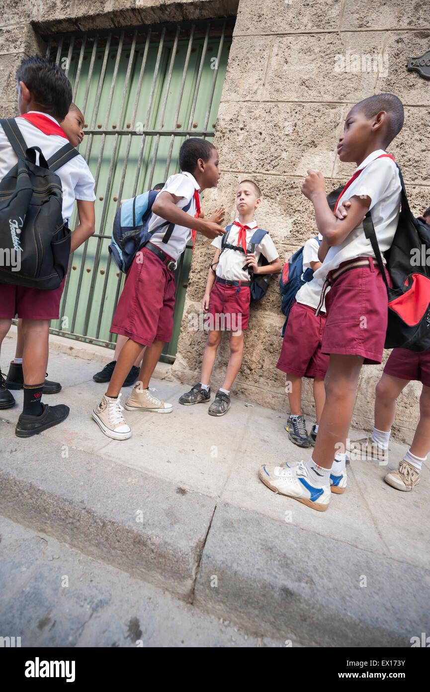 HAVANA, CUBA - JUNE, 2011: Cuban schoolchildren in traditional uniforms gather on a sidewalk outside a school in - Stock Image