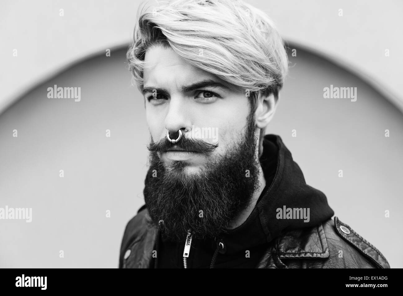 Bearded hipster with nose ring in leather jacket - Stock Image
