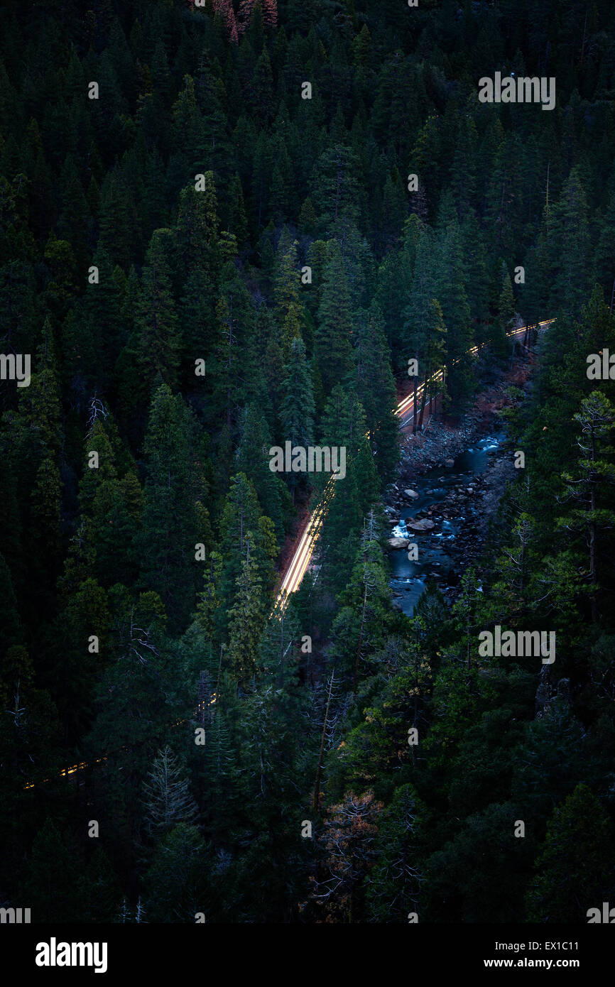 Car headlights at dawn along the Yosemite Valley floor. High shot from above Tunnel View Stock Photo