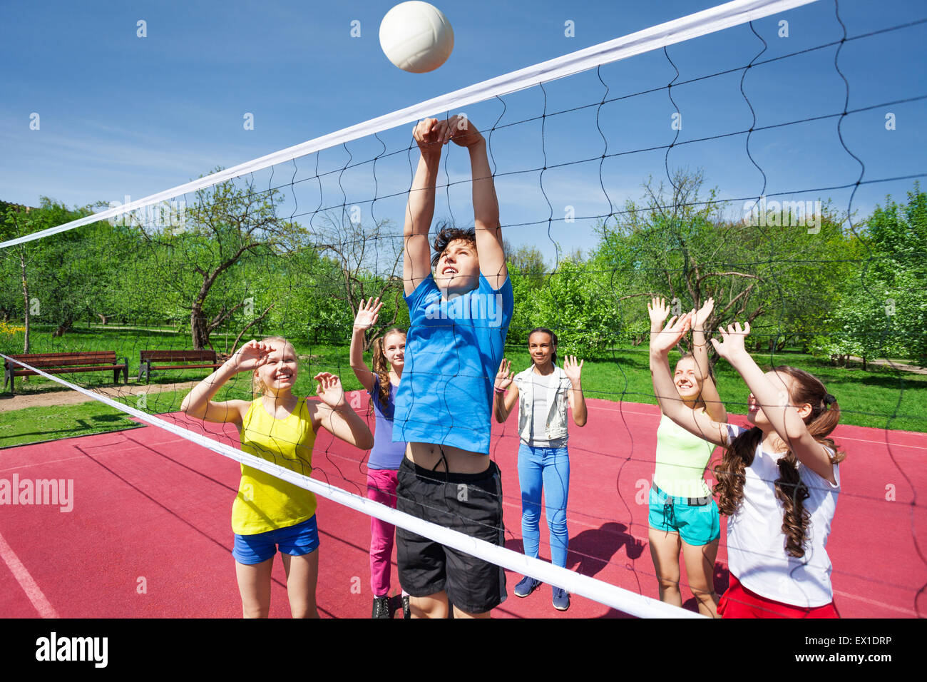 Teens all are with arms up play volleyball - Stock Image