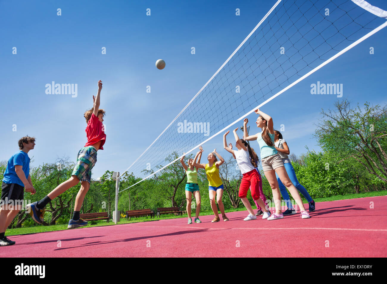 Teenagers play volleyball game on playing ground - Stock Image