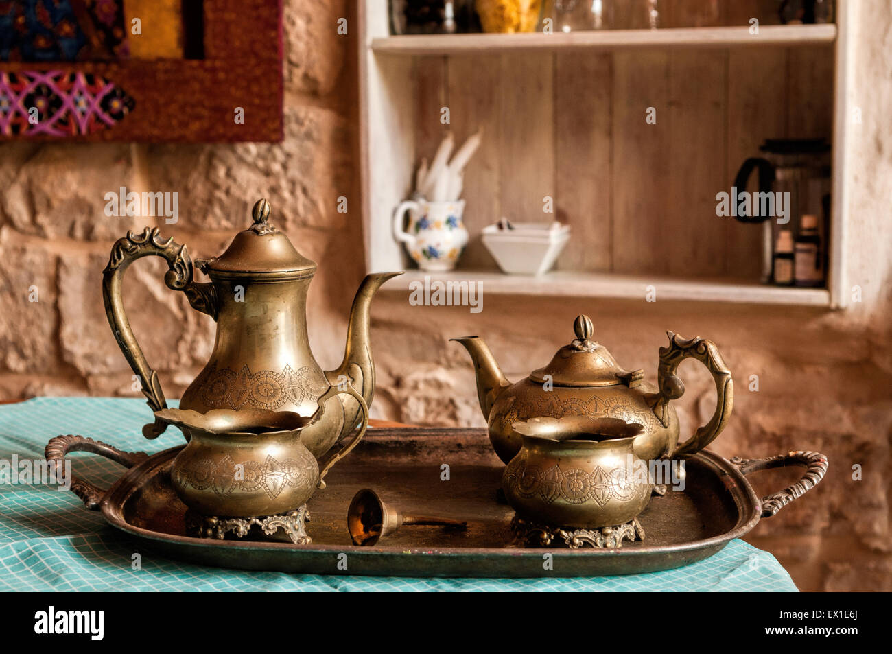 Dinner set of dishes for coffee and tea from the old bronze bell on the tray with the call for workers - Stock Image