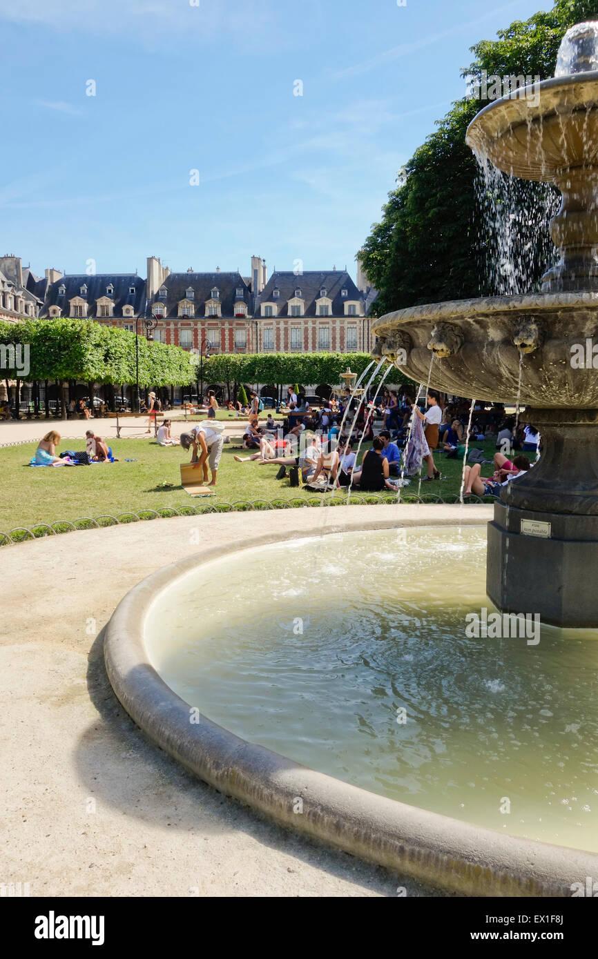 Tourists in summer heat wave near fountain at oldest square, Place de vosges, Paris, France. - Stock Image