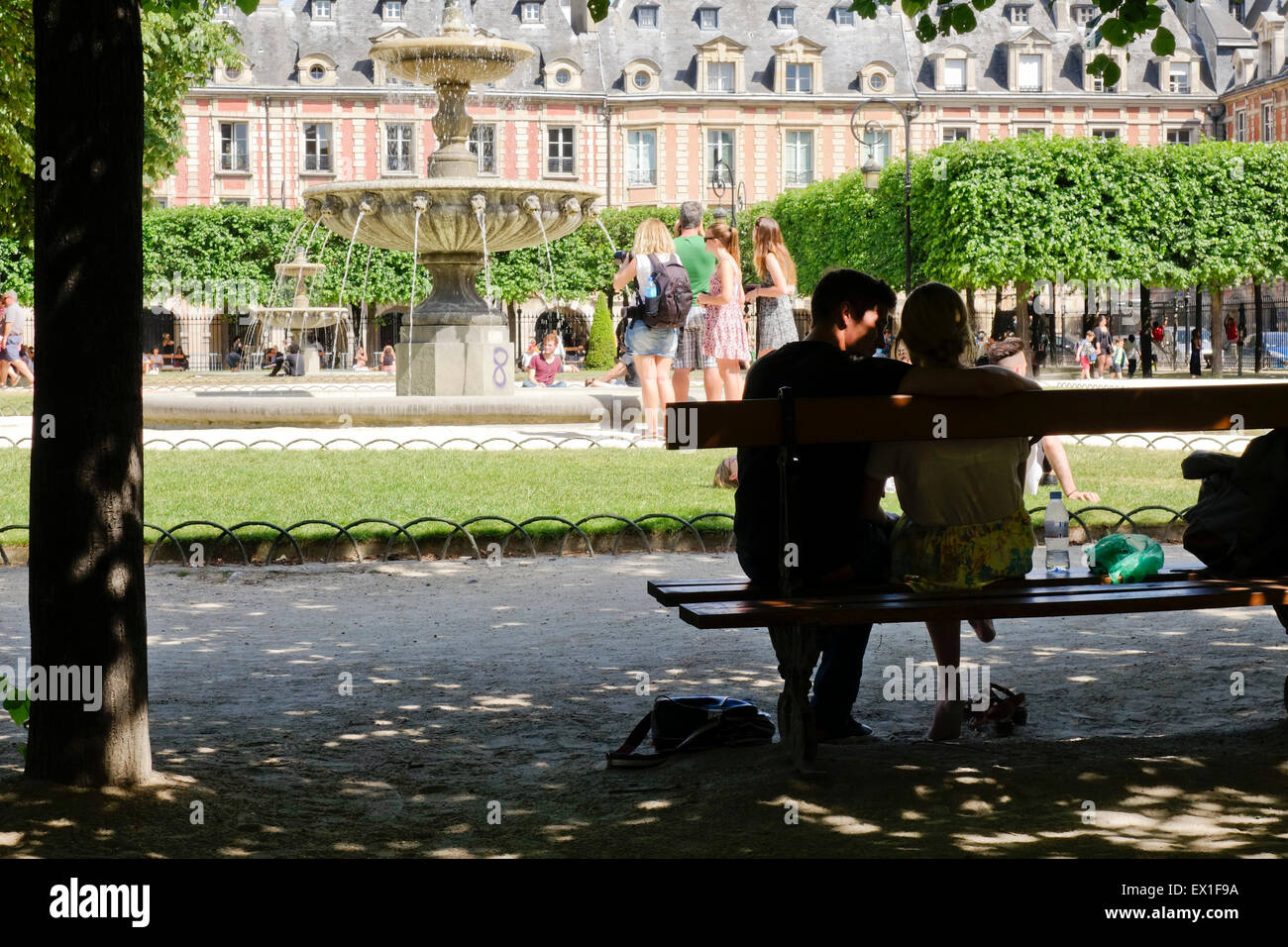 Tourists in summer heat wave near fountain at oldest square, Place de vosges, Paris, France. - Stock Image