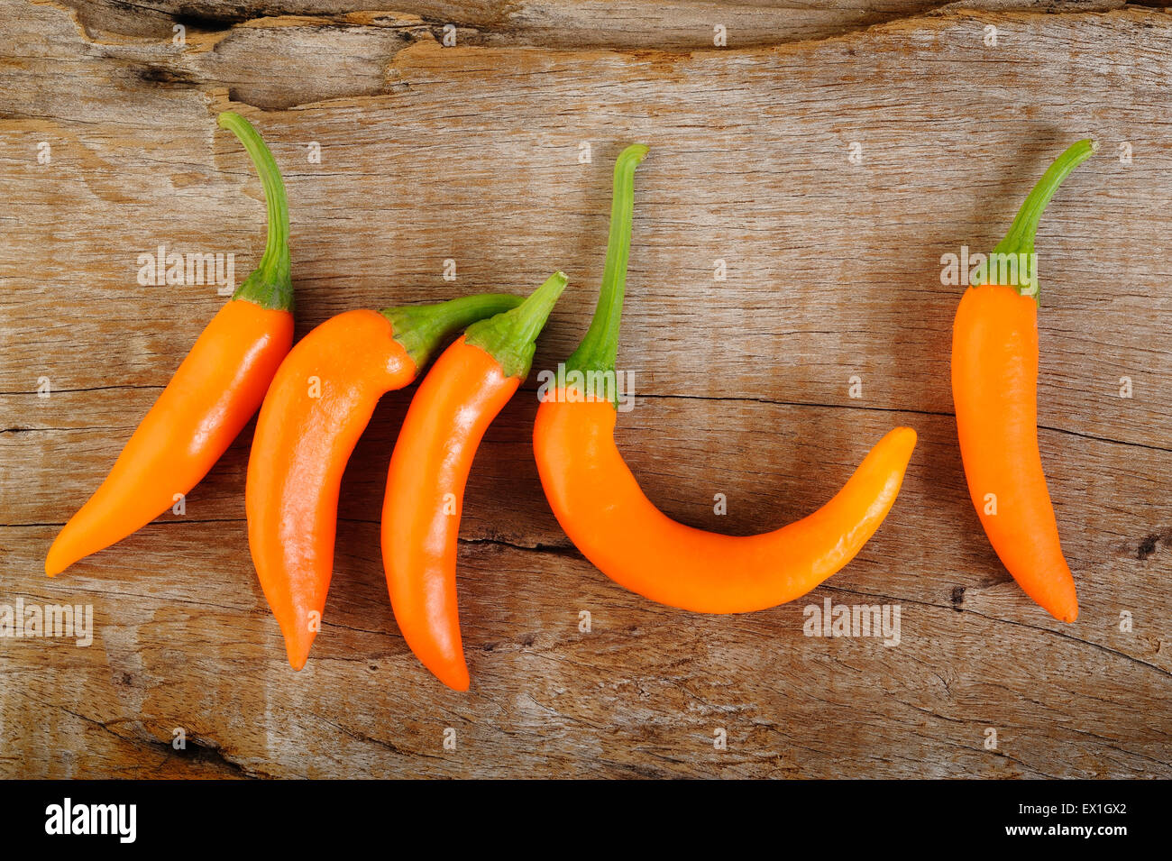 hot chili peppers on old wooden table - Stock Image