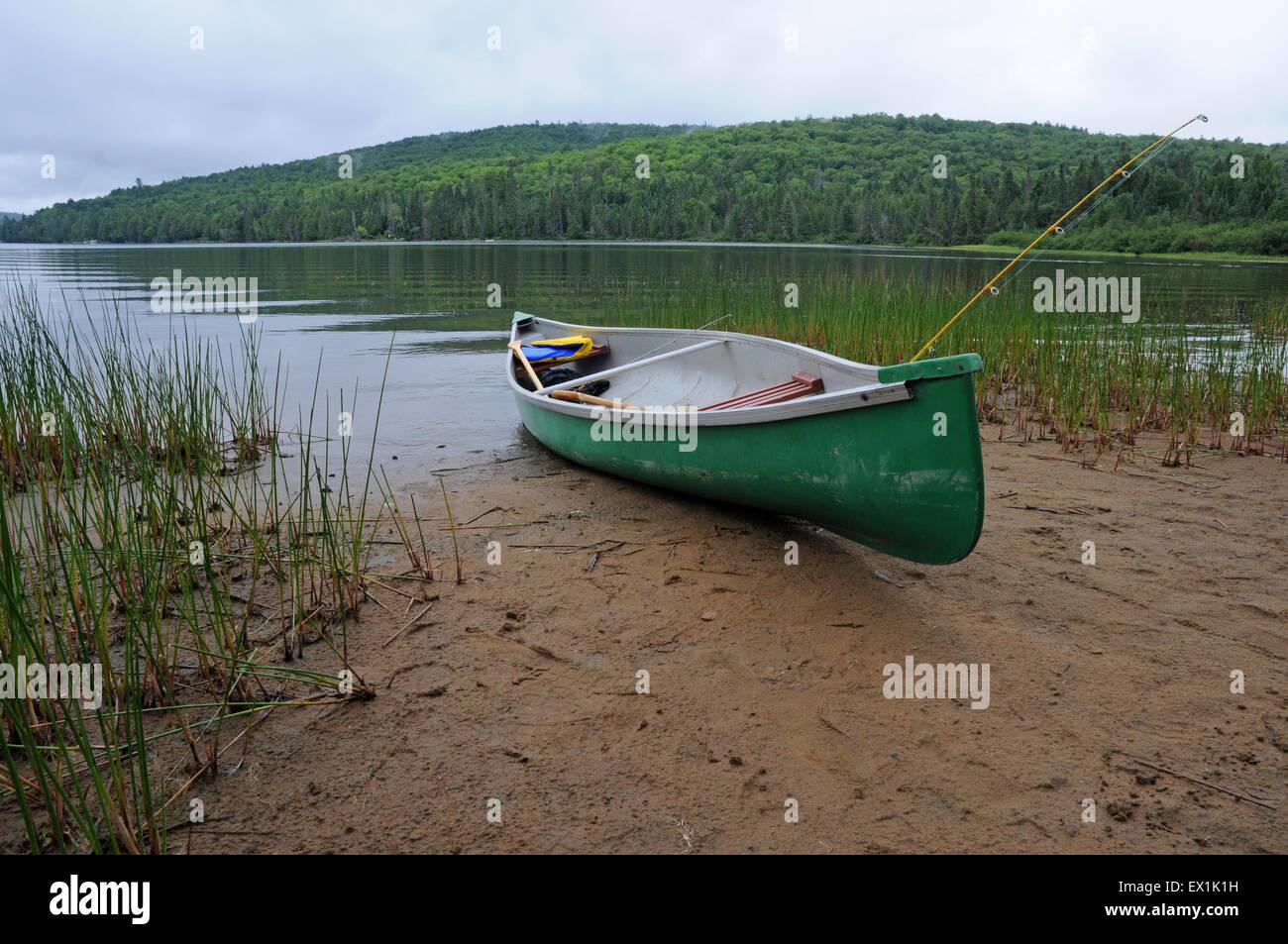 Canoe on edge of a lake - Stock Image