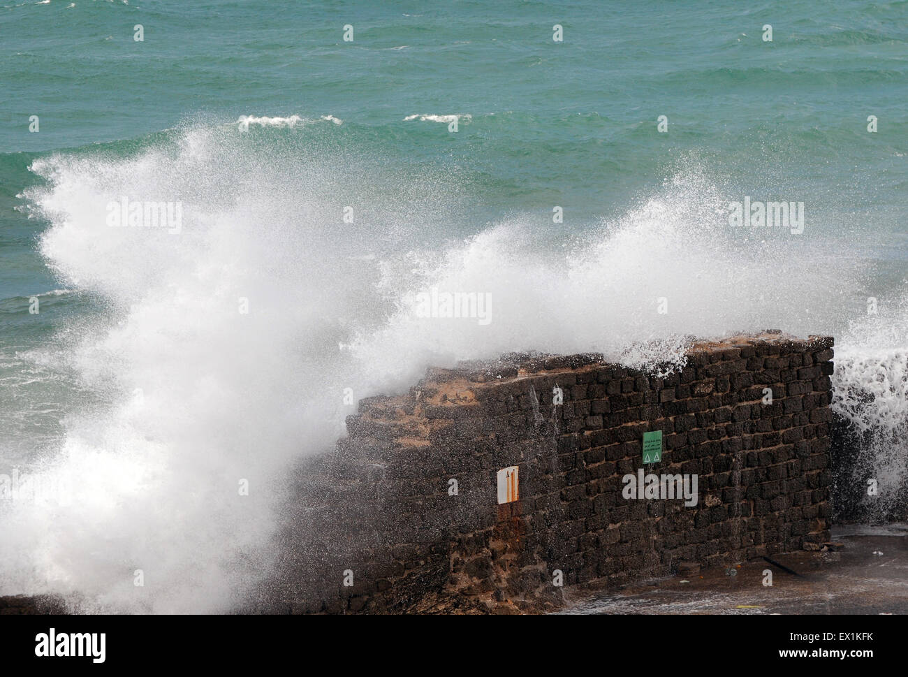 Big storm wave breaking on a stone brick wall - Stock Image