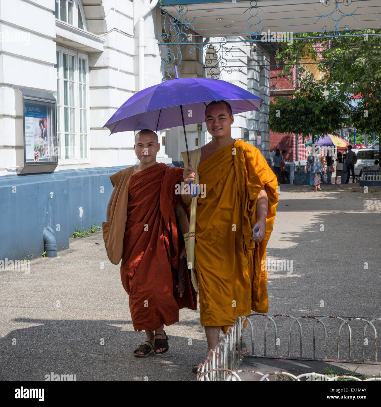 Two Buddhist monks in typical saffron robes walking under a parasol on the Strand in Yangon Myanmar - Stock Image