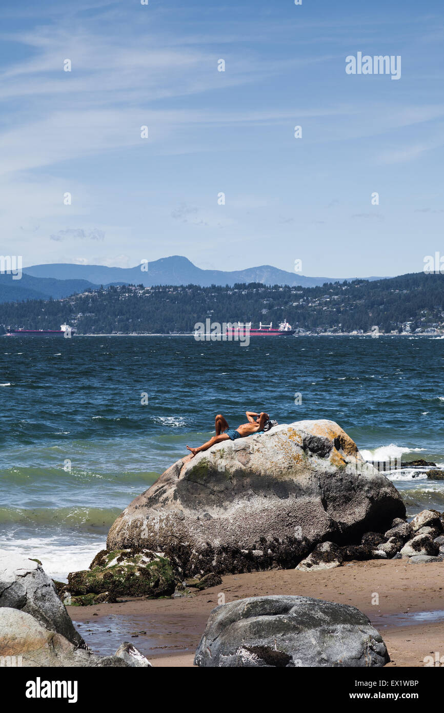 Man laying on a large rock on a sunny day at Stanley Park in Vancouver - Stock Image