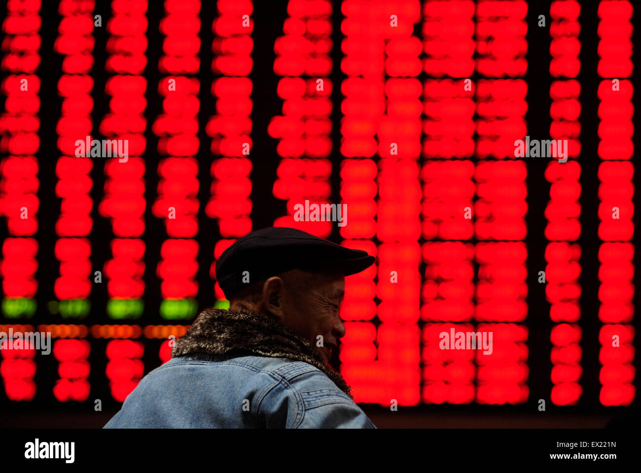An investor gestures in front of an electronic board with stock information at a brokerage house in Hefei, Anhui - Stock Image