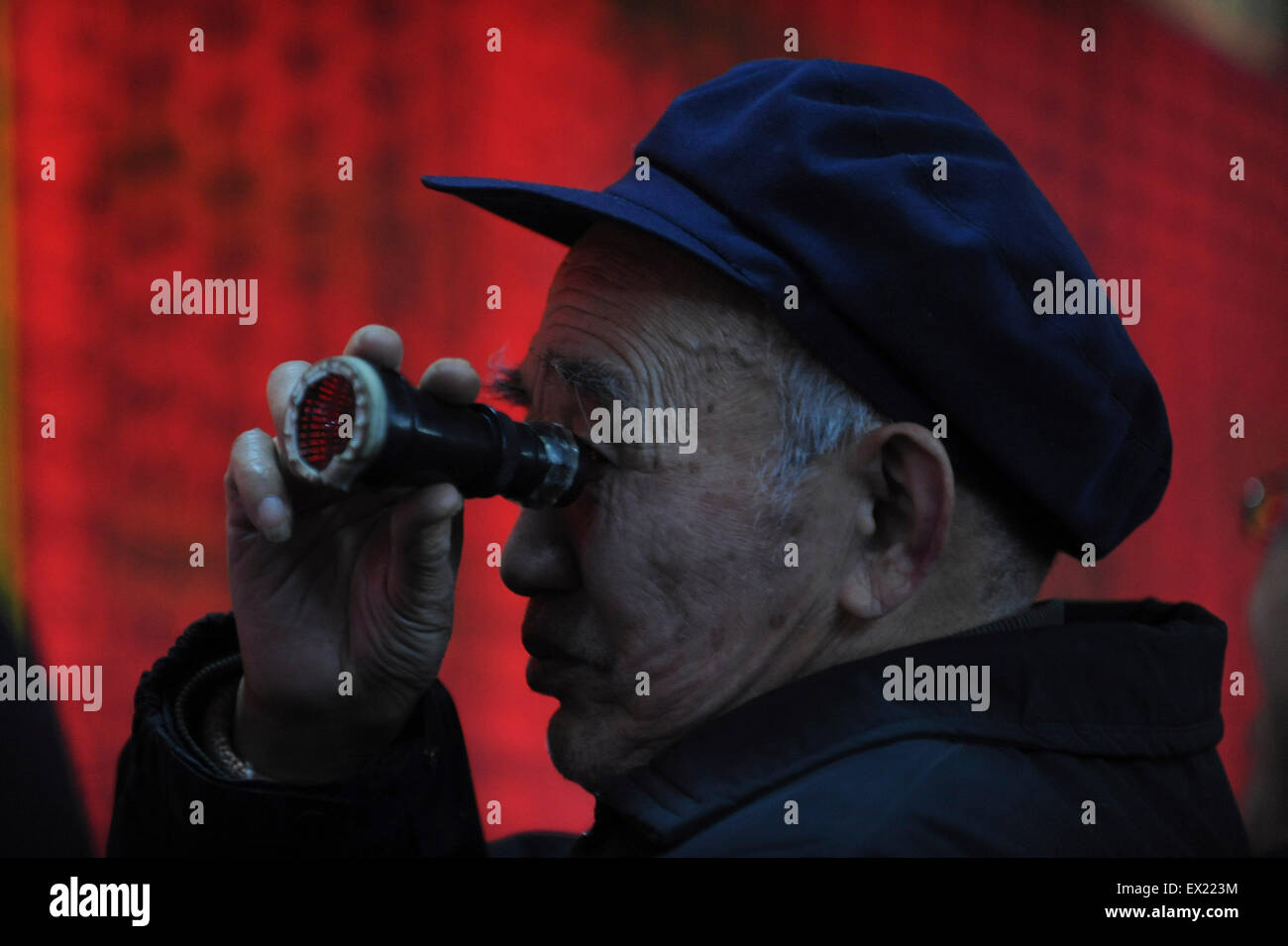 An investor gestures in front of an electronic board with stock information at a brokerage house in Wuhan, Hubei - Stock Image
