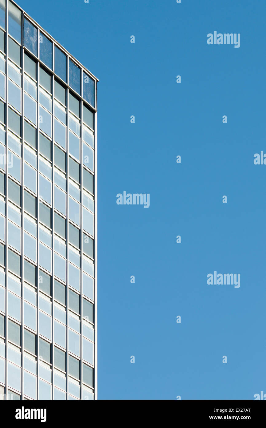 A generic 1950s/60s modern office skyscraper in Manchester with space for copy on blue sky. - Stock Image