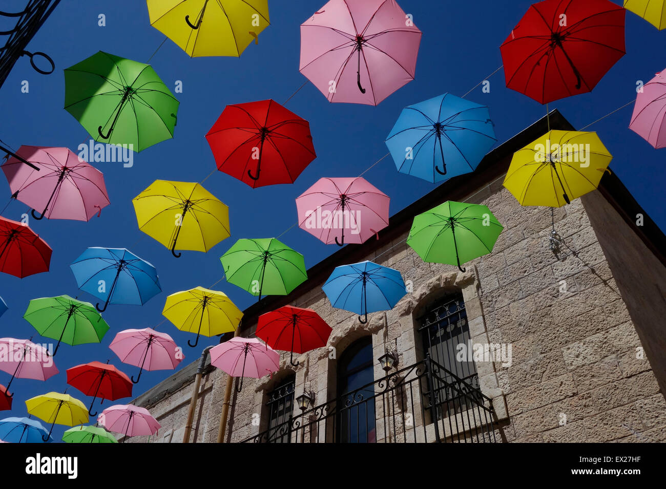 Colorful umbrellas are suspended above Nahalat Shiva alley a pedestrian promenade in West Jerusalem Israel - Stock Image
