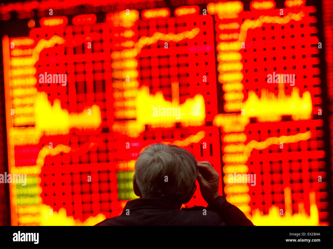 An investor gestures in front of an screen with stock information at a brokerage house in Shanghai February 25, - Stock Image