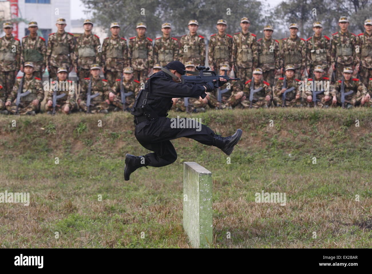 A paramilitary policeman demonstrates shooting while stepping over barriers to recruits during a training session - Stock Image