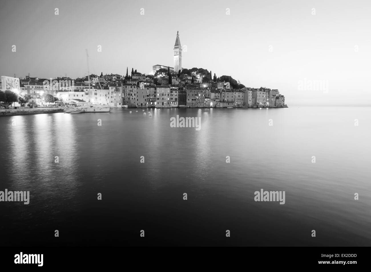 A view of the old city core with the Saint Euphemia church and bell tower at sunset in Rovinj, Croatia. - Stock Image