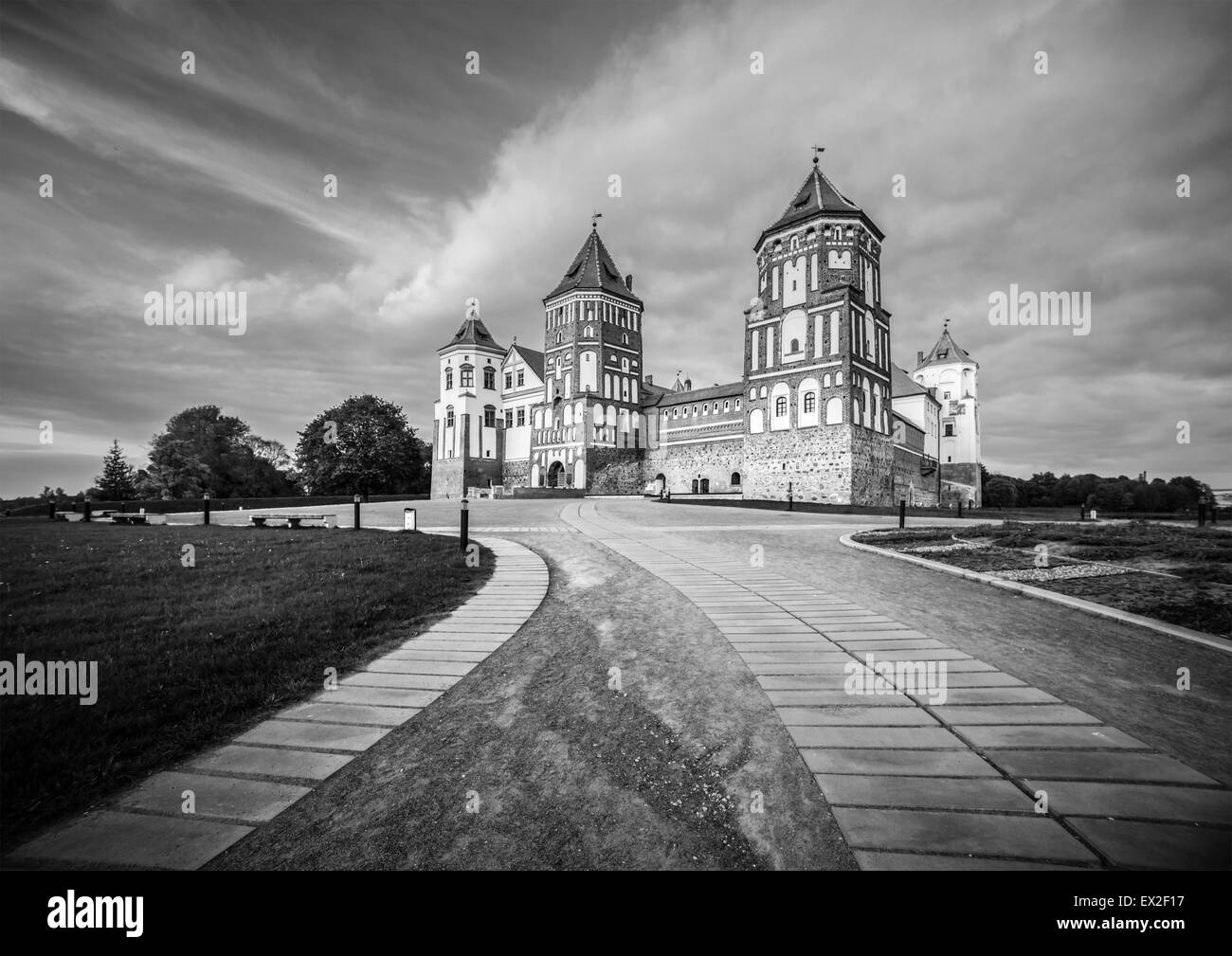 Black and white landscape. Stone road to beautiful Mir castle in Belarus. Medieval fort became sight for tourists. - Stock Image