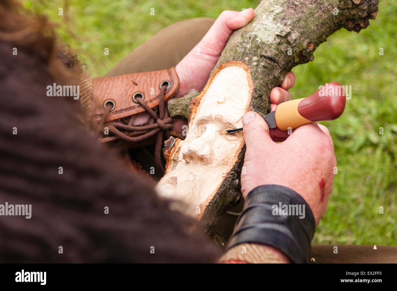 A man dressed in Iron Age clothing whittles a face into a piece of wood - Stock Image