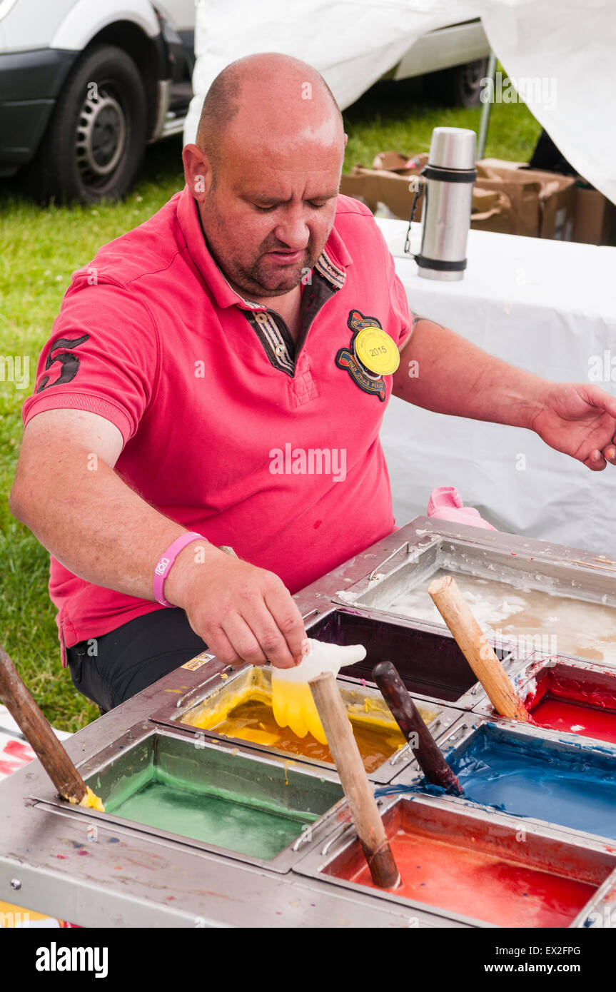 A man makes 'wax hands' using multi coloured waxes at a market - Stock Image