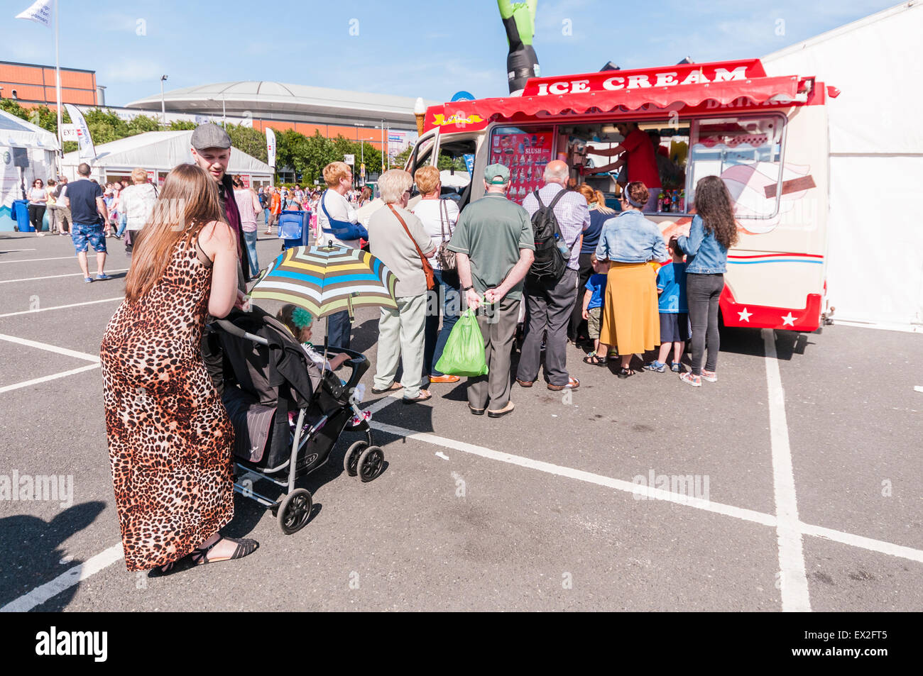 Customers queue up at an ice-cream van on a sunny day - Stock Image
