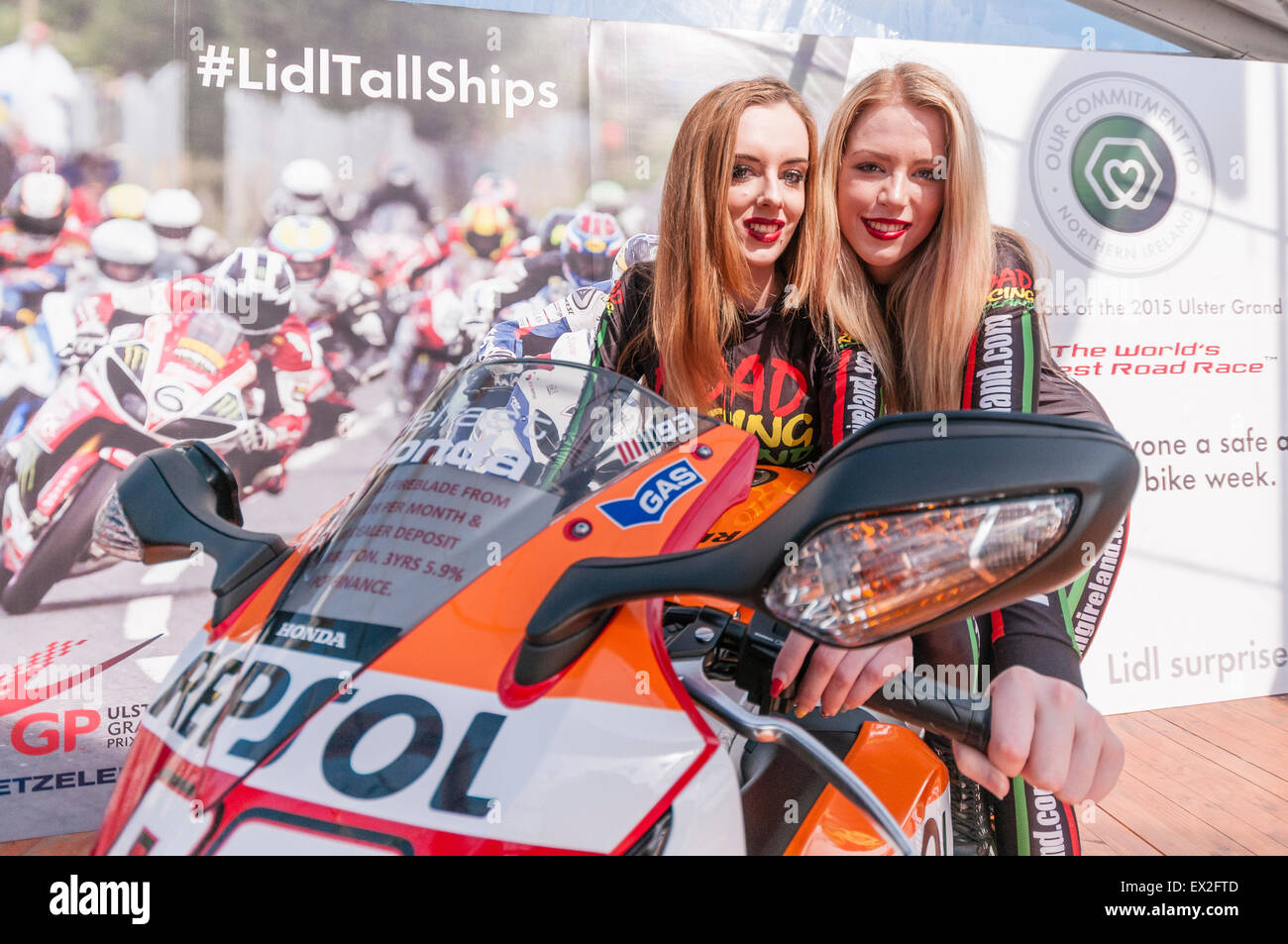Two PR women dressed in racing overalls sit on a Repsol motorbike. - Stock Image