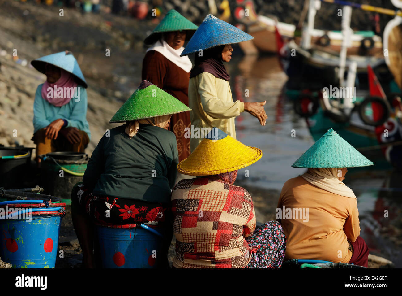 3e7b8271 Unidentified women,traditionally put straw hat on their head, stand and  talk among them while they wait for the fishing boats