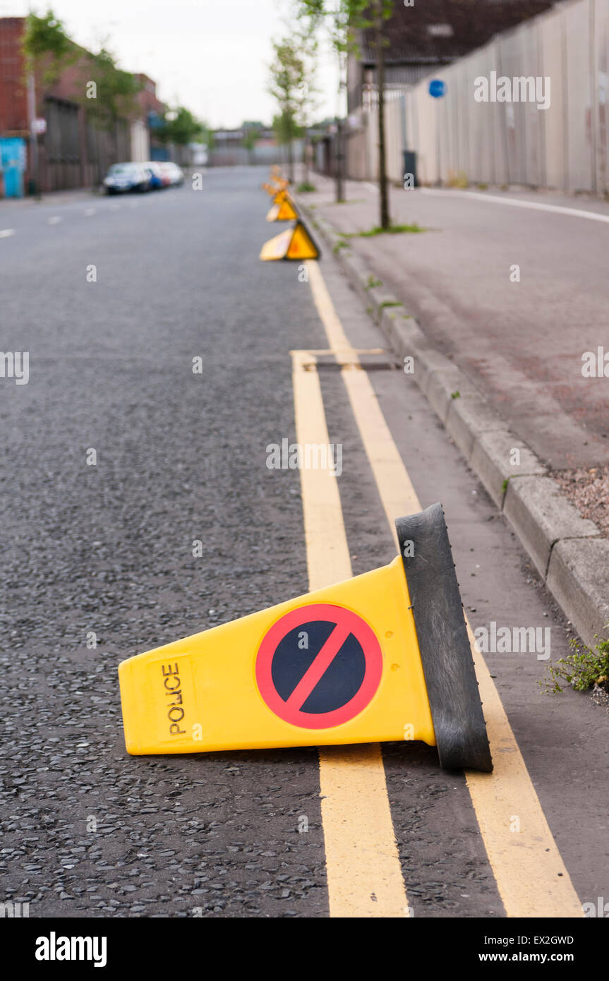 Traffic cones lie on a road after being kicked over by children - Stock Image