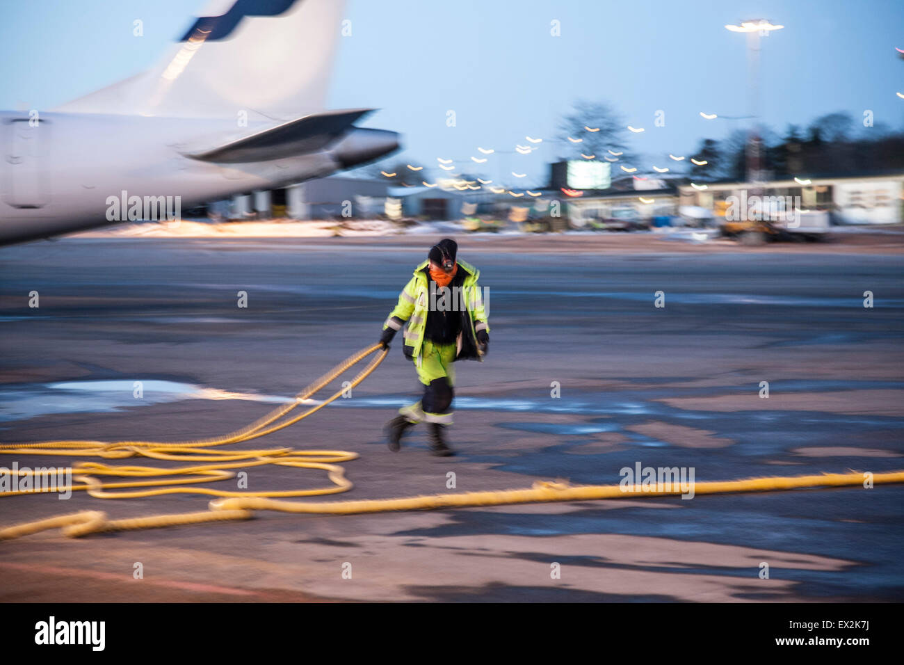 A serviceman on the ground at an airport - Stock Image