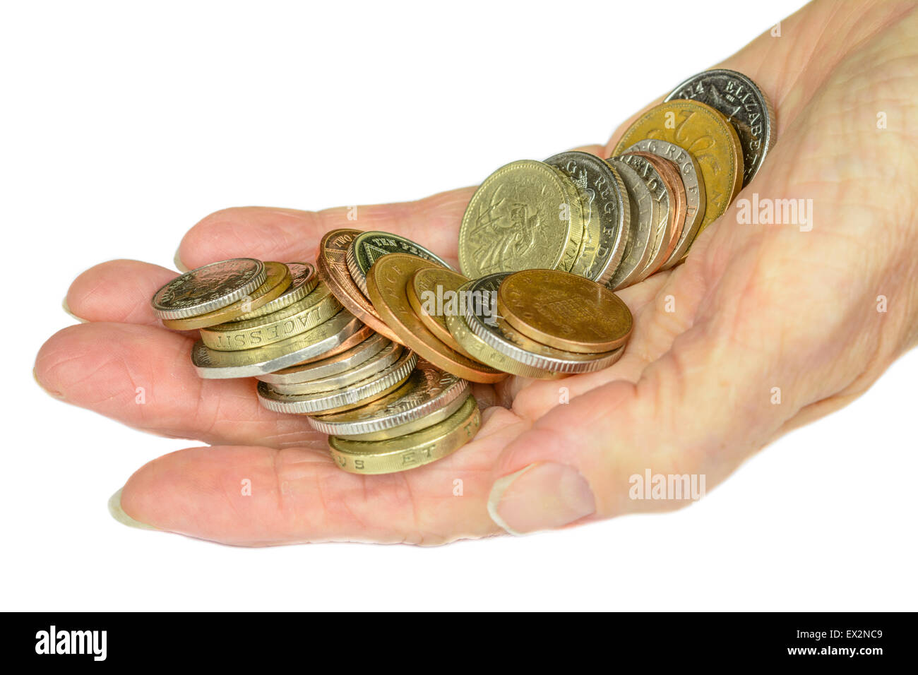 Woman's hand holding UK decimal sterling coins on a white background. - Stock Image