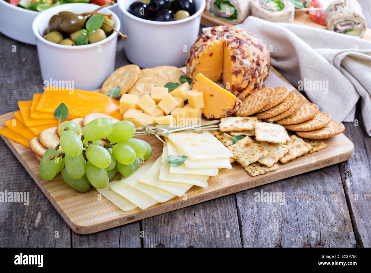Cheese plate with variety of appetizers on table - Stock Image
