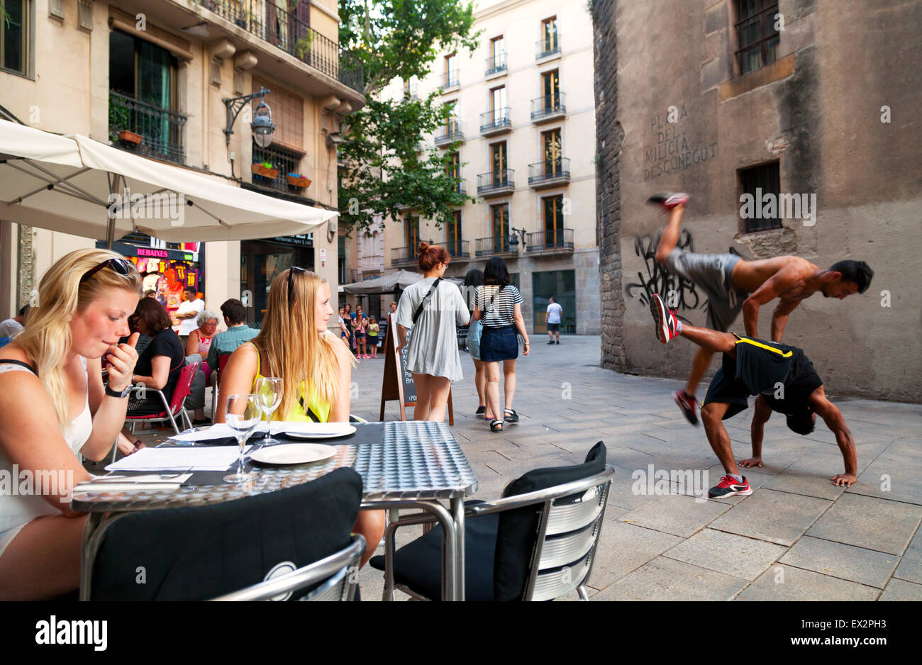 People at a tapas bar watching street entertainers, Placa de Sant Josep Oriol, Gothic Quarter, Barcelona Spain Europe - Stock Image