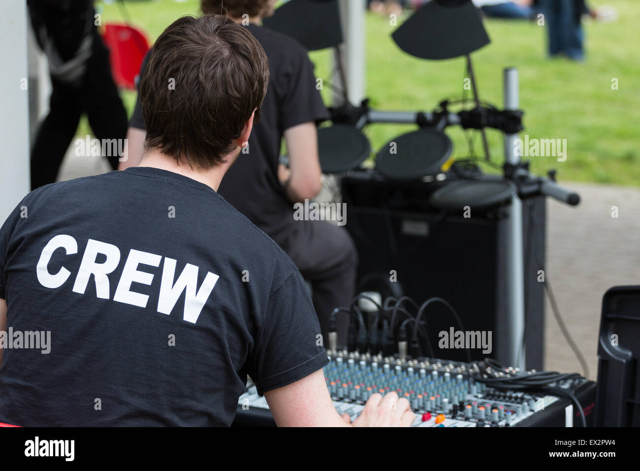 A rock band's sound engineer weras a t-shirt reading 'Crew' - Stock Image