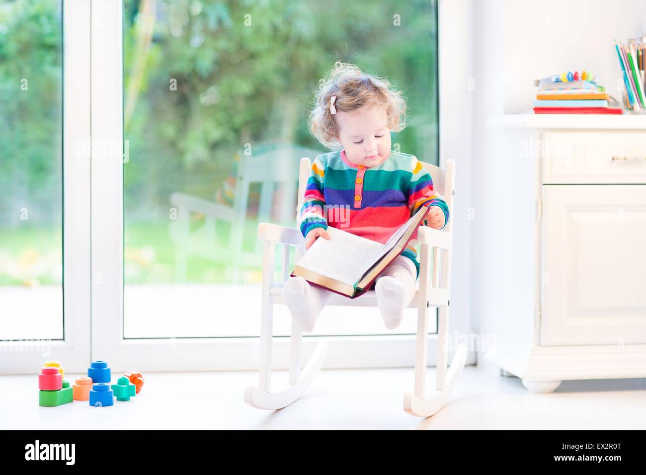 Cute Little Toddler Girl Reading A Book In A White Rocking Chair Next To A  Big Window With Garden View