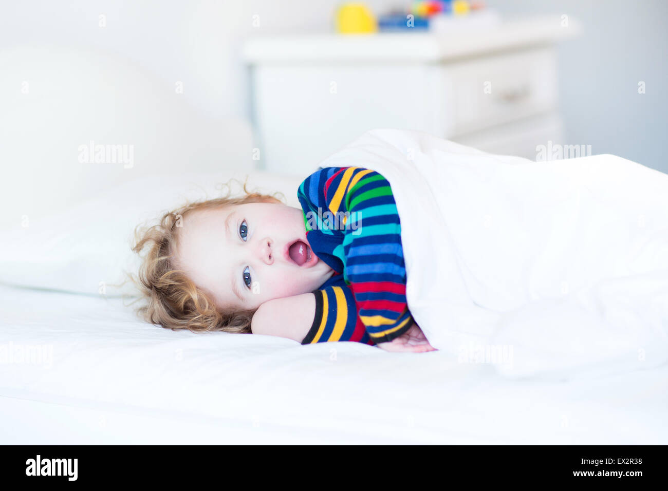 Funny yawning toddler girl waking up in the morning in a sunny white bedroom - Stock Image