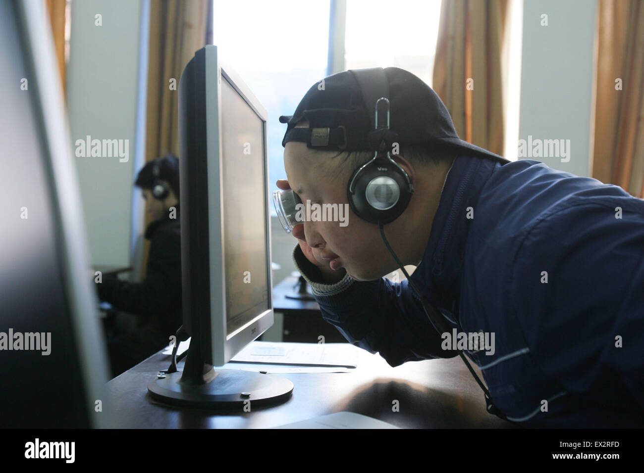 A weak sight man reads questions from computer screen with magnifying glass during a special examination for blind - Stock Image
