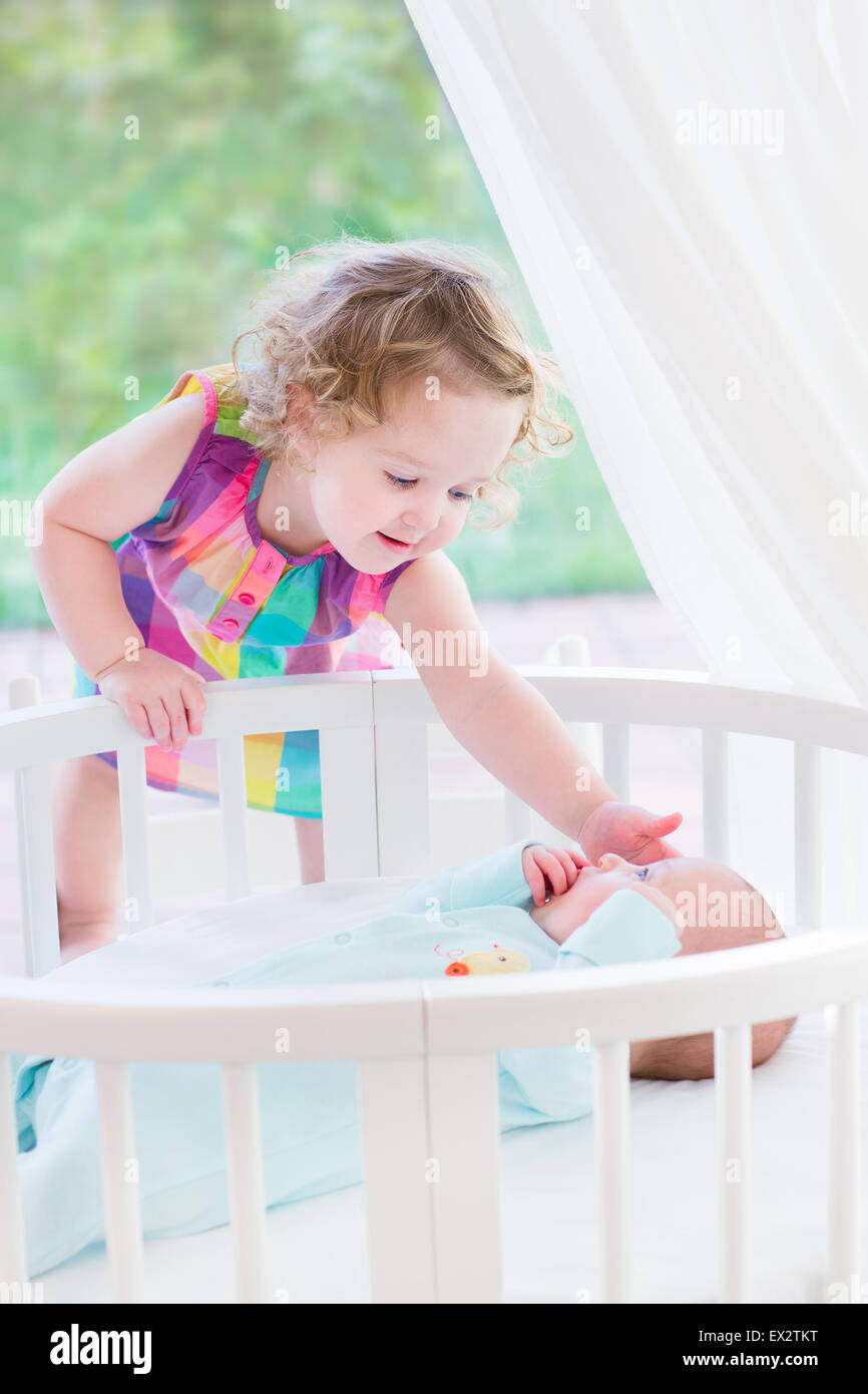 Adorable little toddler girl with curly hair playing with her newborn baby brother in a white round bed next to Stock Photo