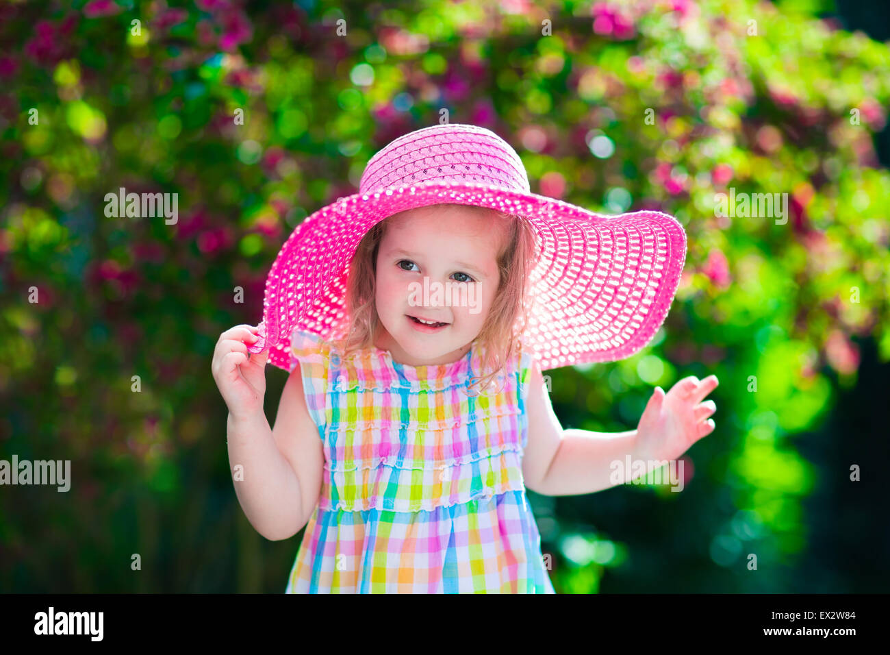 little cute girl with flowers. child wearing a pink hat playing in a
