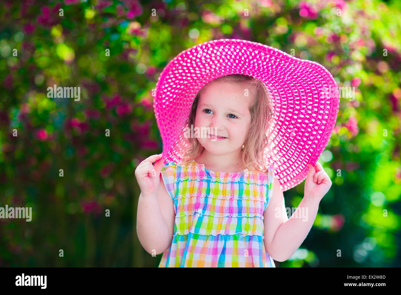 Little cute girl with flowers  Child wearing a pink hat