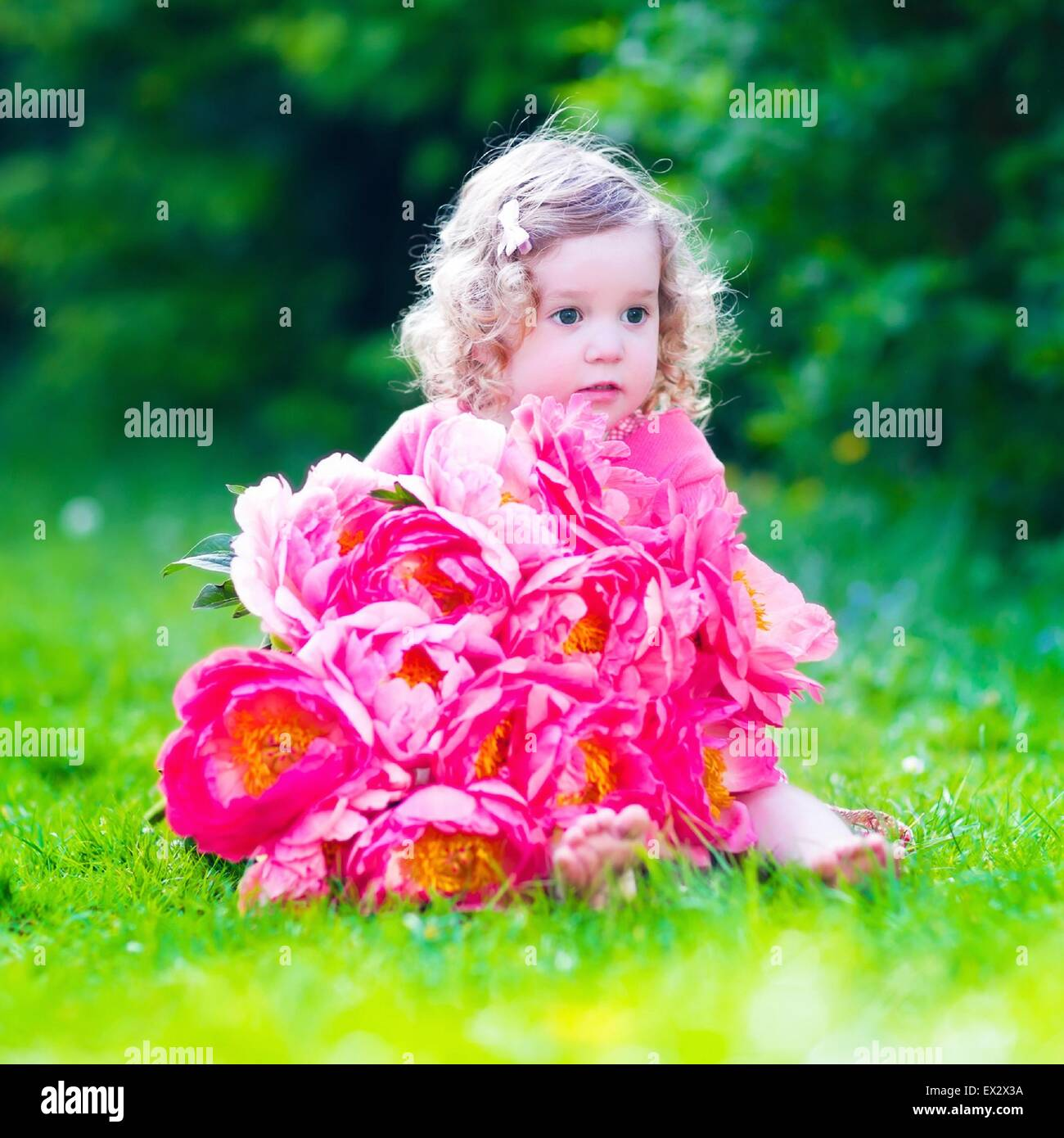 Little Cute Girl With Peony Flowers Child Wearing A Pink Dress