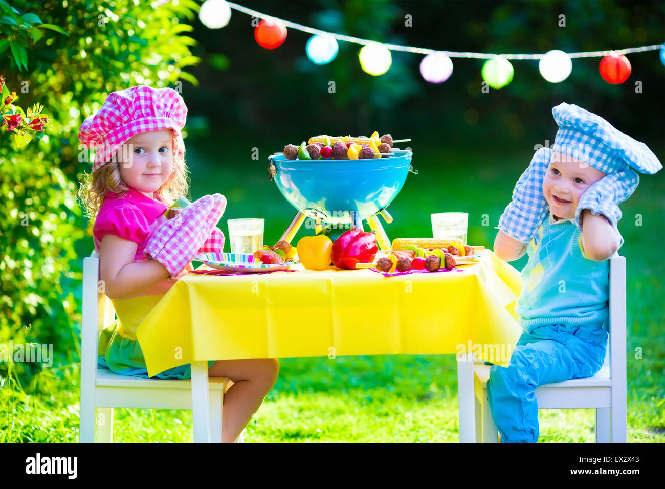 Children grilling meat. Family camping and enjoying BBQ. Brother and sister at barbecue preparing steaks and sausages. - Stock Image